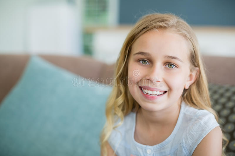 Portrait of a happy girl relaxing on sofa stock photo