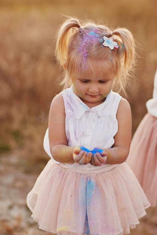 Portrait of happy girl smeared with colored powder. little girl with two tails stock photos