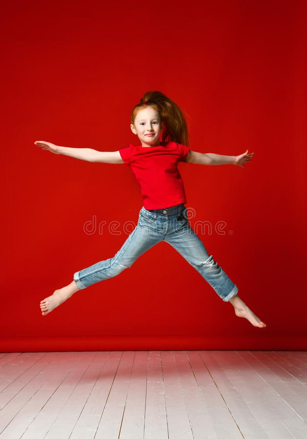 Portrait of happy girl who jumps up high lifting hands isolated on red background stock photos