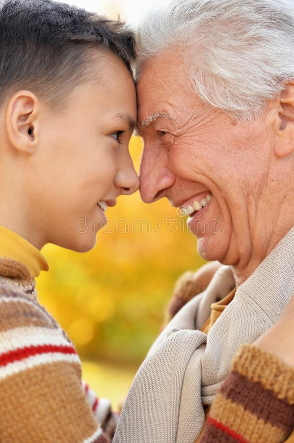 Portrait of happy grandfather and grandson in park royalty free stock photo
