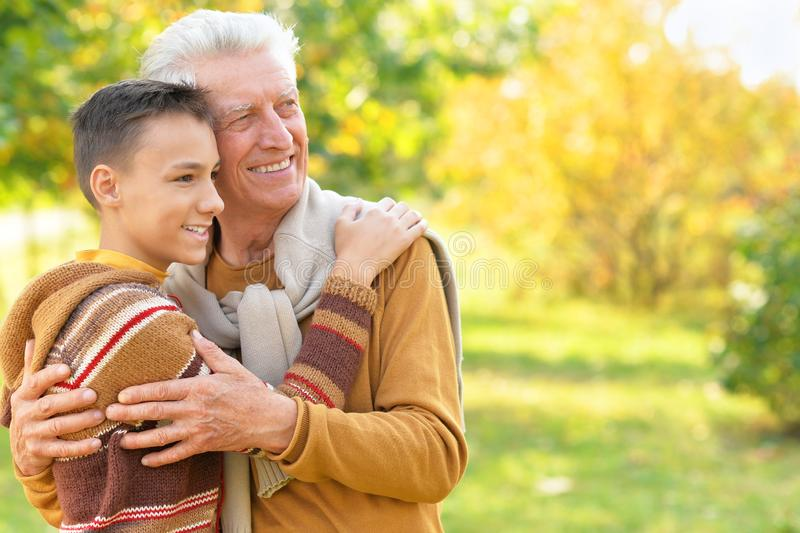 Portrait of happy grandfather and grandson in park royalty free stock image
