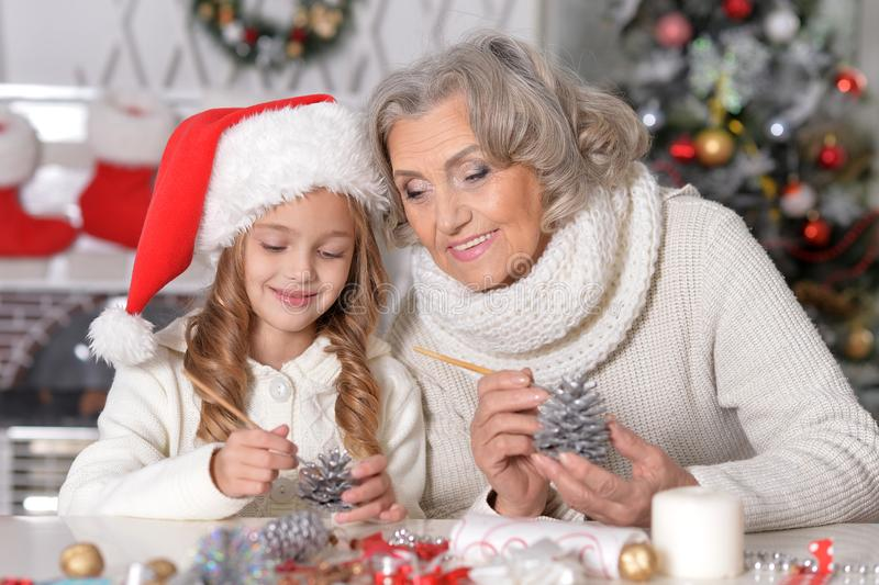 Portrait of happy grandmother and her little granddaughter preparing for Christmas together at home. Painting pine cones royalty free stock photos