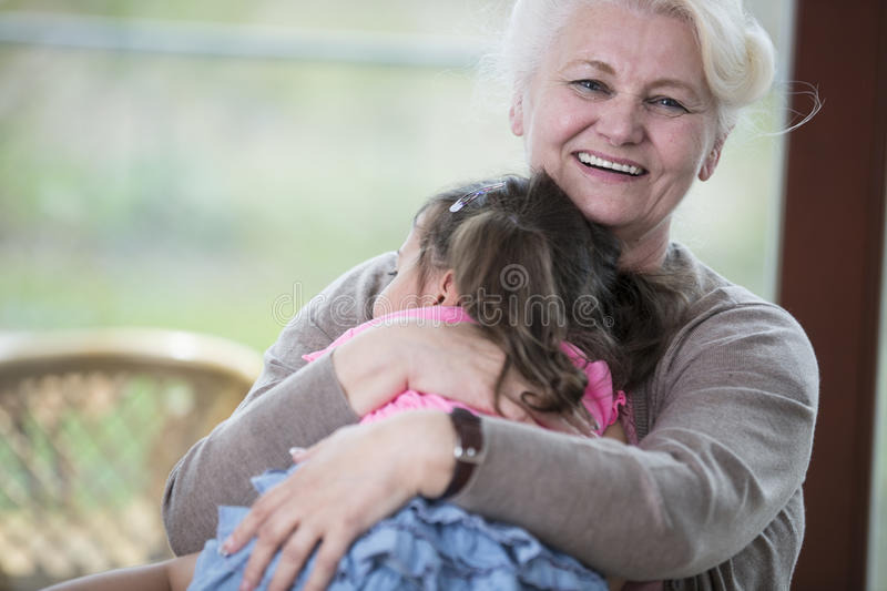 Portrait of happy grandmother hugging granddaughter in house royalty free stock photo