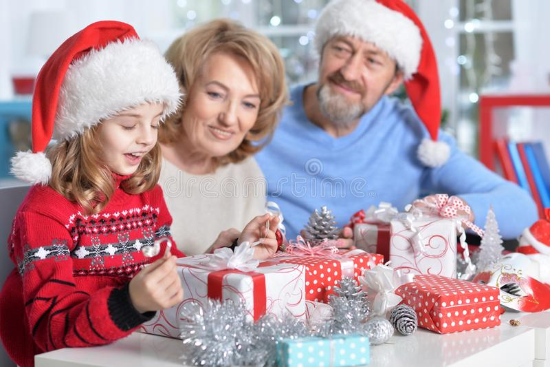 Portrait of happy grandparents with granddaughter preparing for Christmas royalty free stock photography