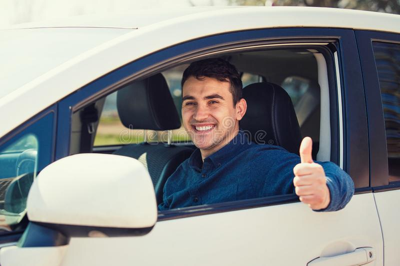 Portrait of happy guy, uber driver showing thumb up positive gesture, smiling gently to camera. Cheerful man driving his new car, excellent acquisition stock photos
