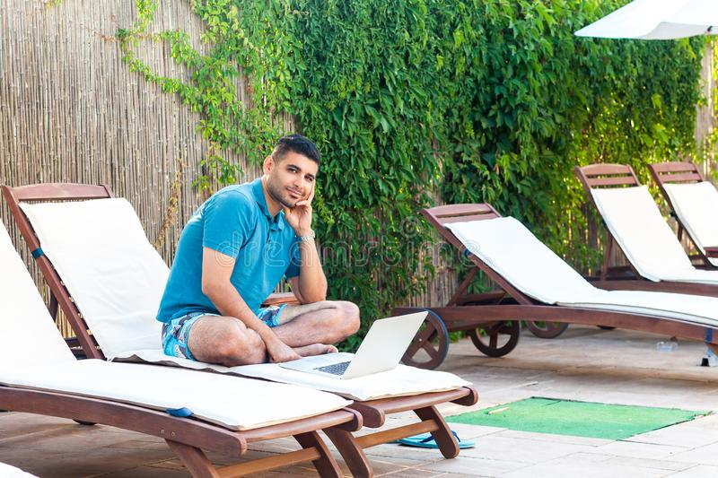 Portrait of happy handsome bearded young adult freelancer man in blue t-shirt and shorts sitting on deckchair with laptop on royalty free stock photography