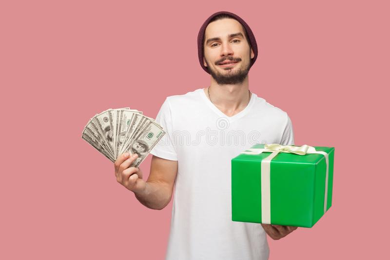 Portrait of happy handsome bearded young hipster man in white shirt and casual hat standing, holding fan of cash dollars and green royalty free stock photos