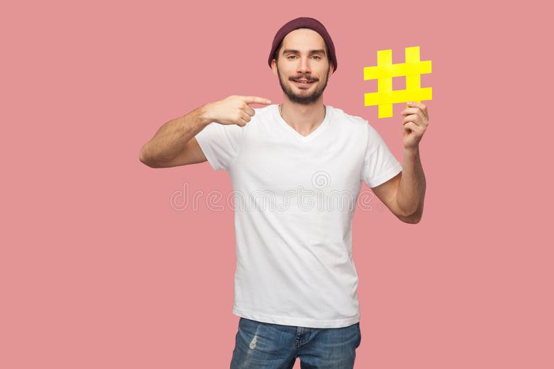 Portrait of happy handsome bearded young hipster man in white shirt and casual hat standing, holding yellow hashtag and pointing stock photos
