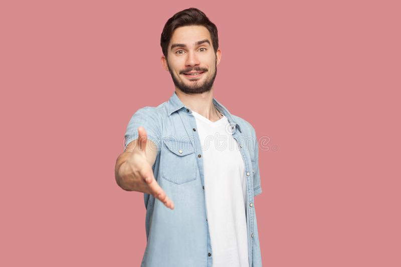 Portrait of happy handsome bearded young man in blue casual style shirt standing, looking at camera with toothy smile and giving. Hand to greeting. indoor royalty free stock images