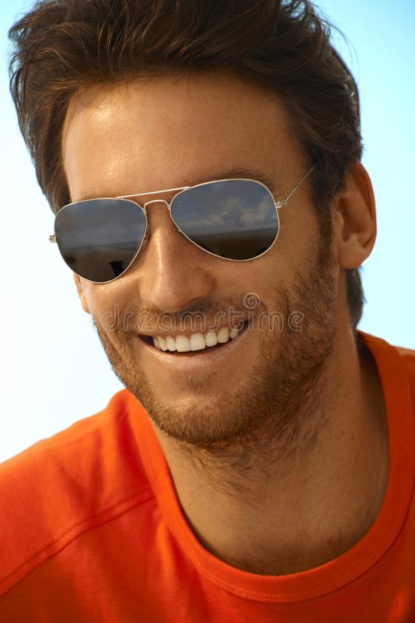 Portrait of happy handsome man wearing sunglasses. Portrait of happy casual handsome caucasian stubbly man wearing sunglasses, mirror shades, aviators. Smiling royalty free stock photo