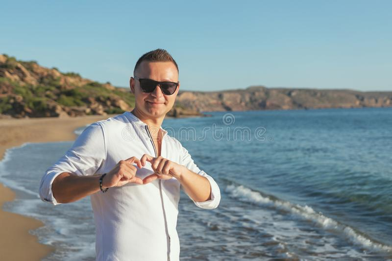 Portrait of happy handsome man in white shirt making heart gesture on the beach. Love concept stock images