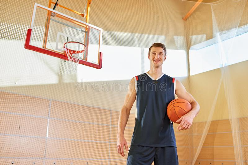 Portrait of happy handsome tall basketball player on court. Jolly successful young Caucasian basketball player in sportswear holding ball against basket and royalty free stock images