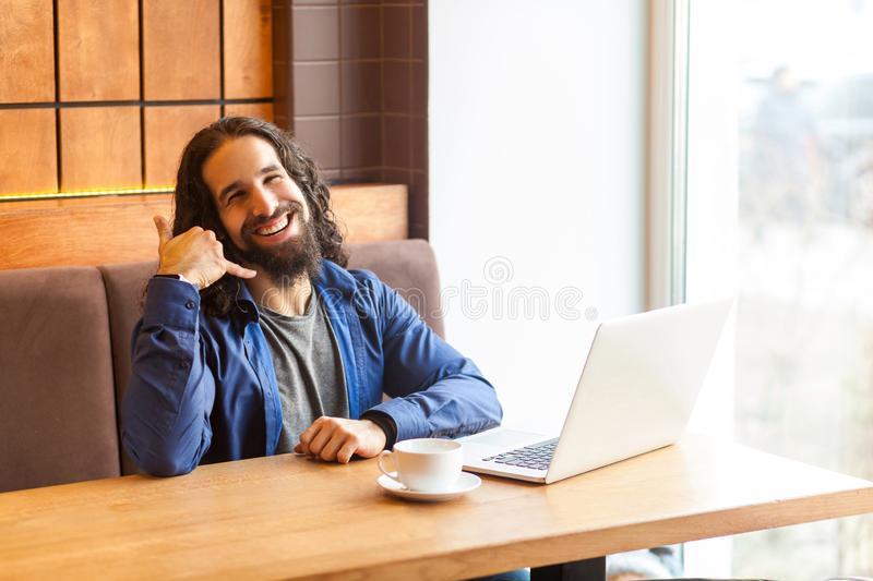 Portrait of happy handsome young adult man freelancer in casual style sitting in cafe with laptop, showing to make call him later. Looking at camera, toothy royalty free stock images