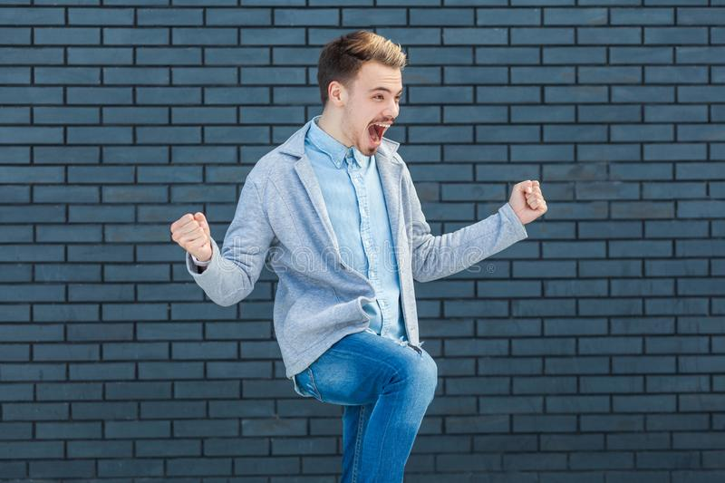 Portrait of happy handsome young blonde man in casual style standing, amazed, celebrating and rejoicing his victory and success royalty free stock photo