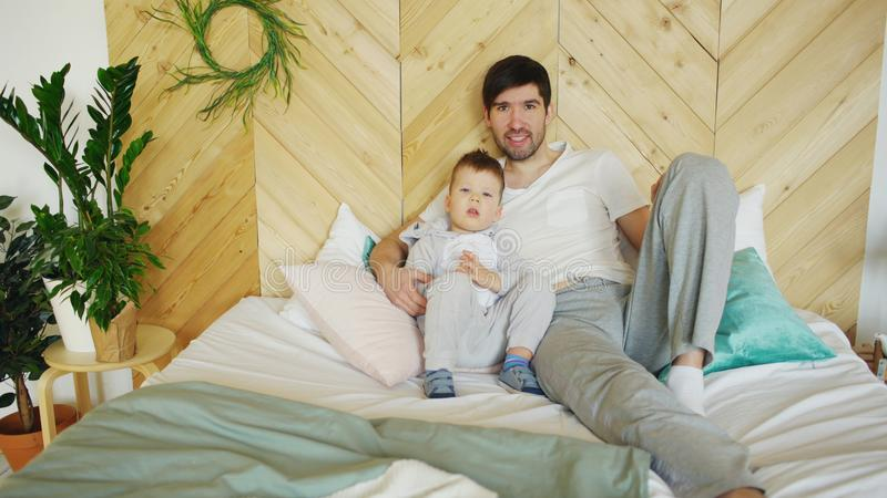 Portrait of happy handsome young father and his son lying on bed smiling and posing into camera. In bedroom at home royalty free stock photography