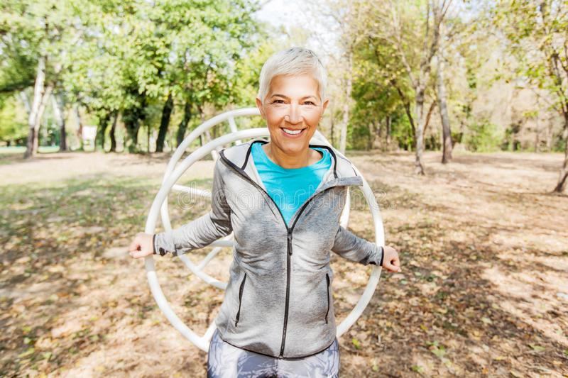 Happy Healthy Senior Woman Workout At Outdoor Gym In Nature stock images