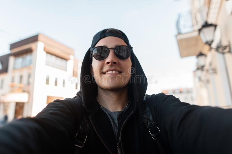 Portrait of a happy hipster man in a fashionable sweatshirt with a hood in stylish sunglasses and a cap. With a camera in his hands in the city near the royalty free stock image