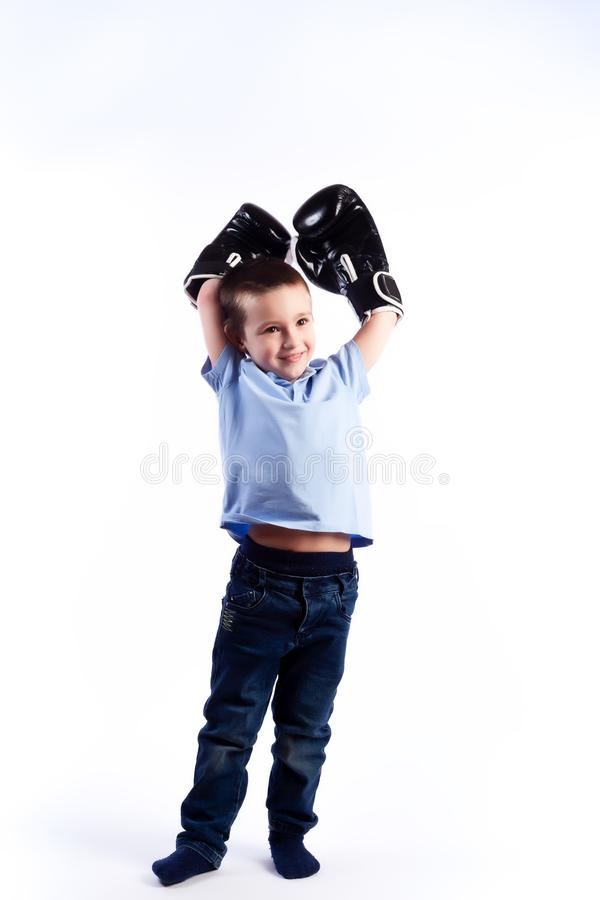 Portrait of happy joyful beautiful boy. A little boy with dark hair in blue jeans, a blue polo shirt in black and white boxing gloves is having fun, showing stock images