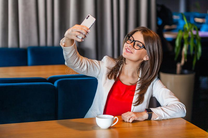 Portrait of happy joyful beautiful stylish brunette young woman in glasses sitting on video call or doing selfie with toothy smile royalty free stock images