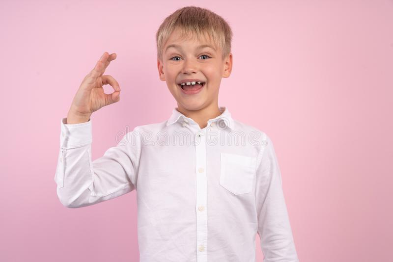 Portrait of happy joyful little boy smiling and showing ok sign. studio portrait over pink background. wearing white shirt stock images