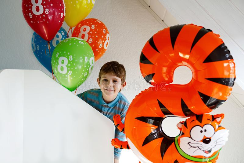 Portrait of happy kid boy with bunch on colorful air balloons on 8 birthday. Smiling school child having fun, celebrating seventh birth day. Family and best stock photography