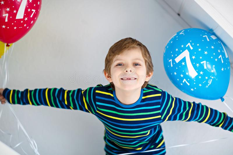 Portrait of happy kid boy with bunch on colorful air balloons on 7 birthday. Smiling school child having fun, celebrating seventh birth day. Family and best royalty free stock photo