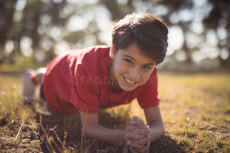 Portrait of happy kid performing exercise during obstacle course royalty free stock images