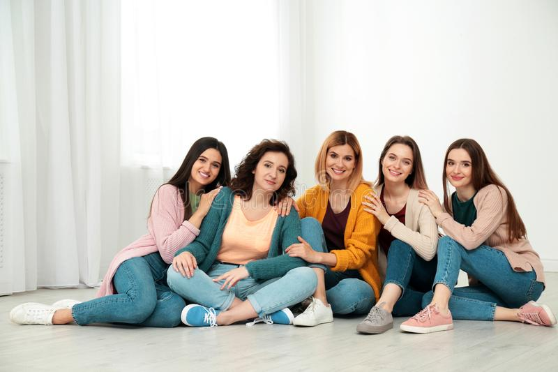 Portrait of happy ladies sitting on floor. Women power concept. Portrait of happy ladies sitting on floor indoors. Women power concept stock photos