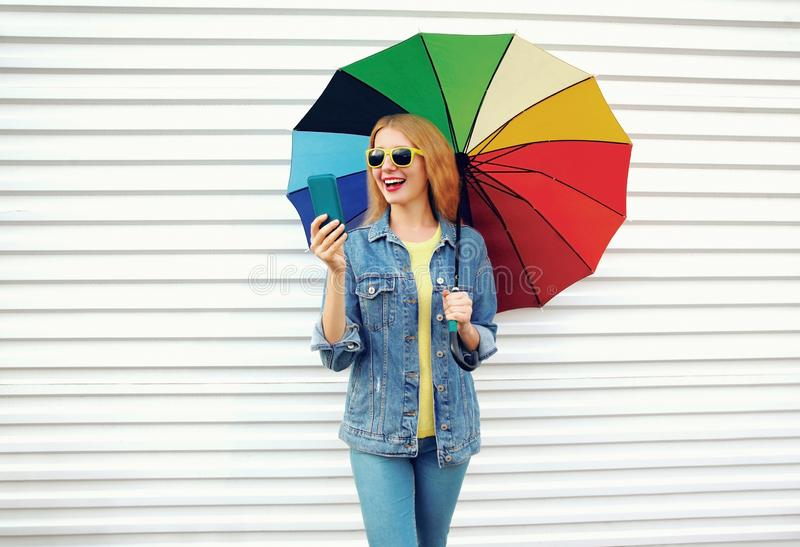 Portrait happy laughing surprised woman with colorful umbrella, phone on white wall background stock images