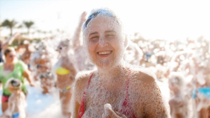 Portrait of happy laughing young woman in red bikini dancing on the sea beach. Girl having fun on sea beach soap foam royalty free stock photography