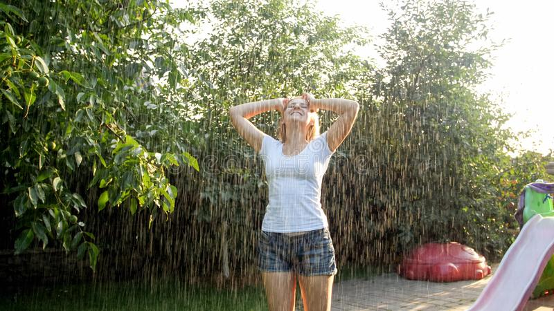Portrait of happy laughing young woman with long hair in wet clothes dancing under warm rain in garden. Family playing royalty free stock images
