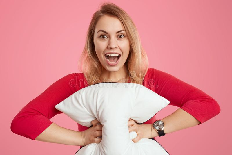 Portrait of happy light haired young woman with overjoyed facial expression, holds soft white pillow, dressed in red jumper, opens stock photo