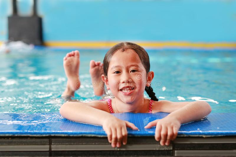 Portrait of happy little Asian child girl learning to swim in pool. Close-up short royalty free stock photography