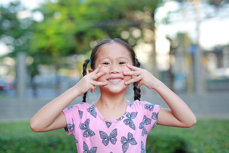 Portrait of happy little Asian child girl show finger in shape of look like a cat on her face in the garden royalty free stock photo