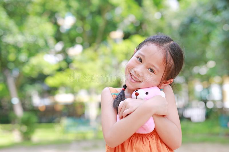 Portrait of happy little Asian child in green garden with hugging teddy bear and looking at camera. Close up smiling kid girl in royalty free stock image