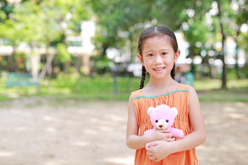Portrait of happy little Asian child in green garden with hugging teddy bear and looking at camera. Close up smiling kid girl in royalty free stock photo