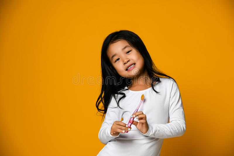 Portrait of a little girl holding a tooth brush over yellow background royalty free stock photography