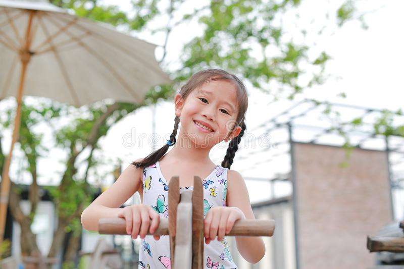 Portrait of happy little Asian girl playing wooden toy horse in the garden outdoor stock images