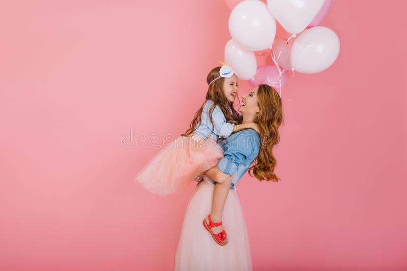 Portrait of happy little birthday girl with long hair holding balloons and hugging her young stylish mom after event royalty free stock images