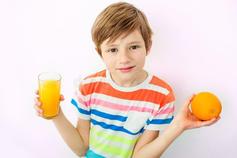 Portrait of happy little boy drinking orange juice. stock images