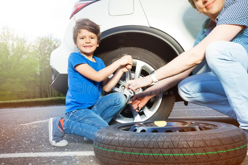 Little boy helping his father to change car wheel stock photography