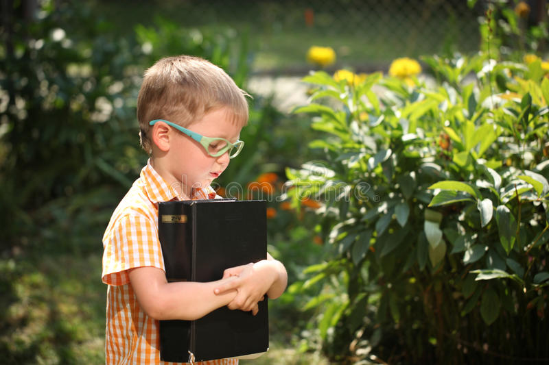 Portrait Happy little boy holding a big book on his first day to school or nursery. Outdoors, Back to school concept stock photo
