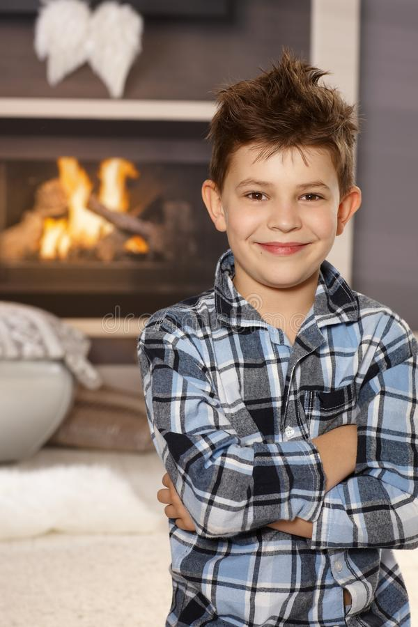 Portrait of happy little boy at home. Confident happy little boy standing arms crossed in living room, smiling, looking at camera royalty free stock photography