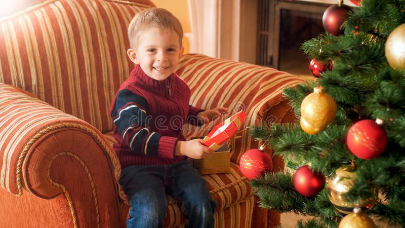 Portrait of happy cheerful little boy sitting in armchair and opens his Christmas present box from Santa Claus royalty free stock images