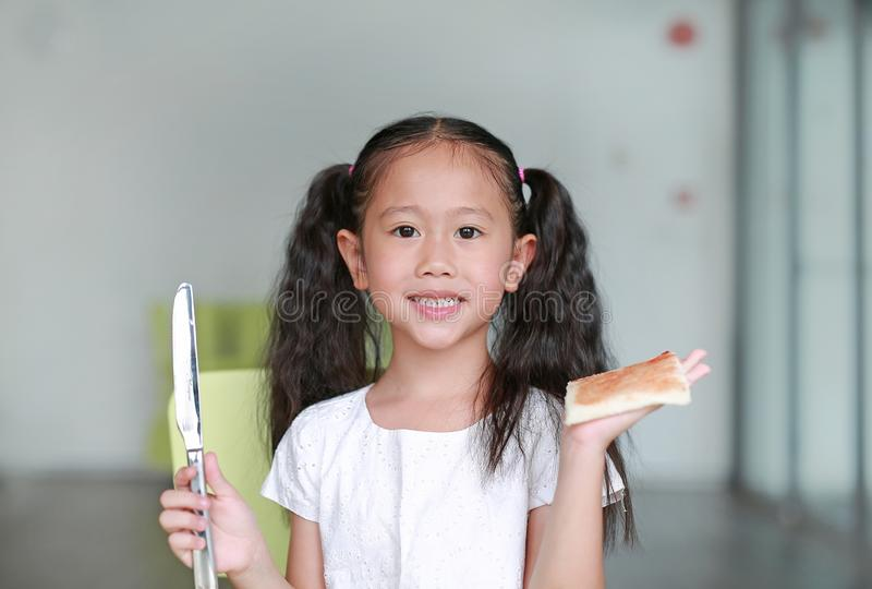 Portrait happy little child girl cooking at class room. Children show an apply strawberry jam on bread.  stock photo