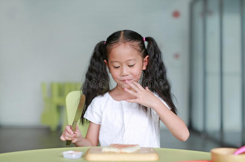 Portrait happy little child girl cooking at class room. Kid taste strawberry jam while cooking. Children are using knife slicing. And apply jam on bread on stock photography