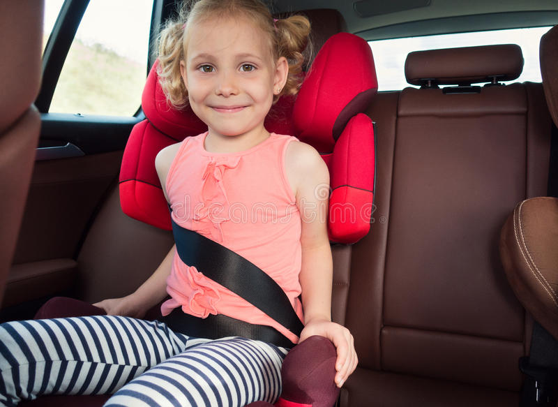 Portrait of happy little child girl sitting comfortable in car s stock photos