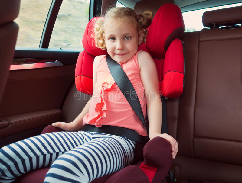 Portrait of happy little child girl sitting comfortable in car s royalty free stock image