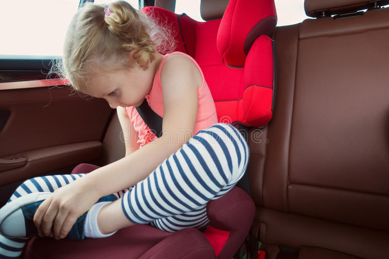 Portrait of happy little child girl sitting comfortable in car s stock photography