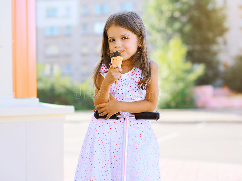 Portrait happy little child with sweet ice cream on the scooter stock image